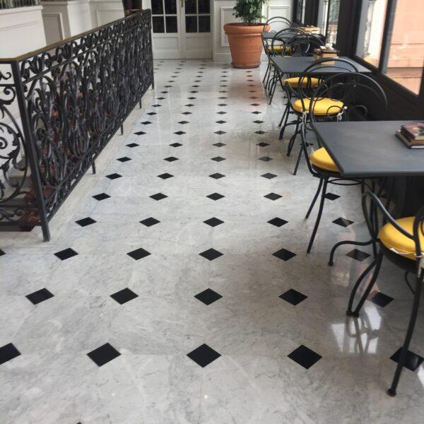 Vackert golv i carrara marmor med tosetter i svart marmor